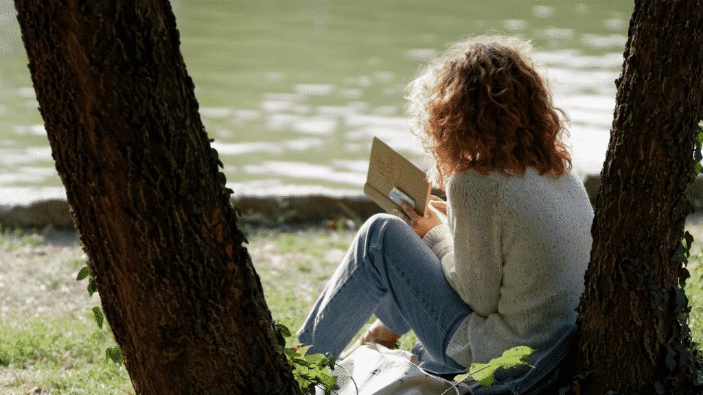 Mulher de costas sentada embaixo da árvore lendo um livro