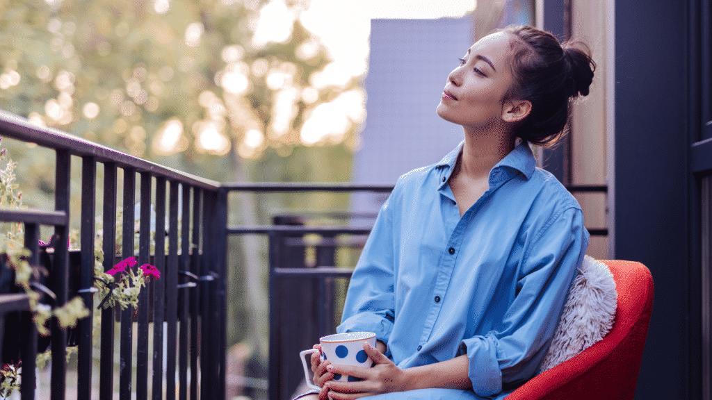 Moça refletindo enquanto toma uma xícara de chá