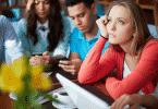 Menina pensativa no meio de pessoas mexendo no celular