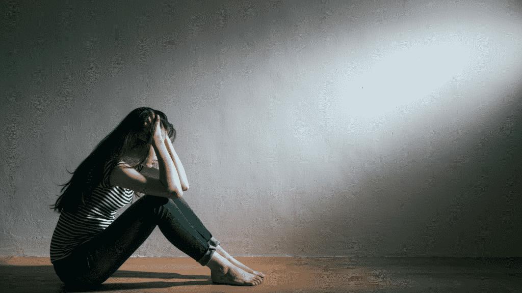 Menina sentada no chão com as mãos na cabeça