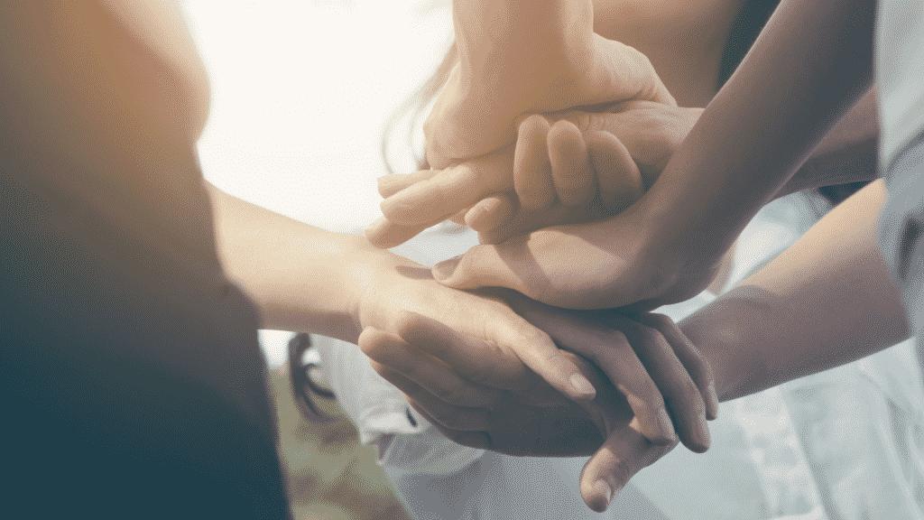 Pessoas colocando as mãos uma sobre as outras