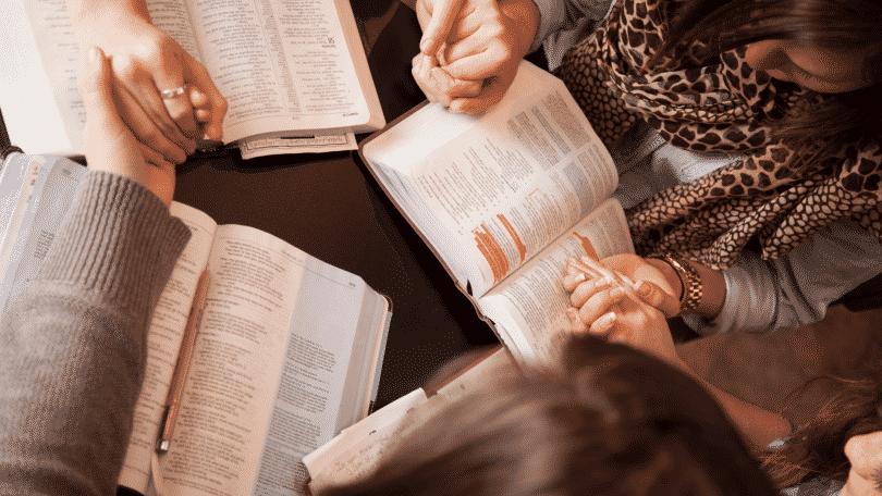 Grupo de oração rezando dando as mãos com bíblias no colo