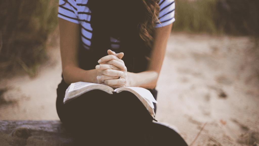 Mulher orando de mãos juntas sobre a bíblia
