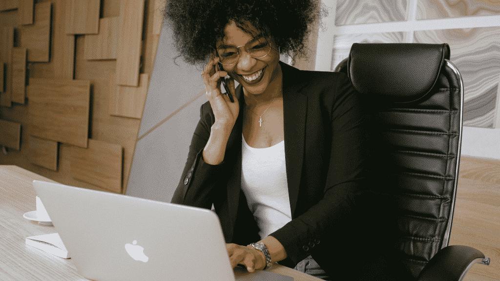 Mulher alegre trabalhando em escritório enquanto fala no celular