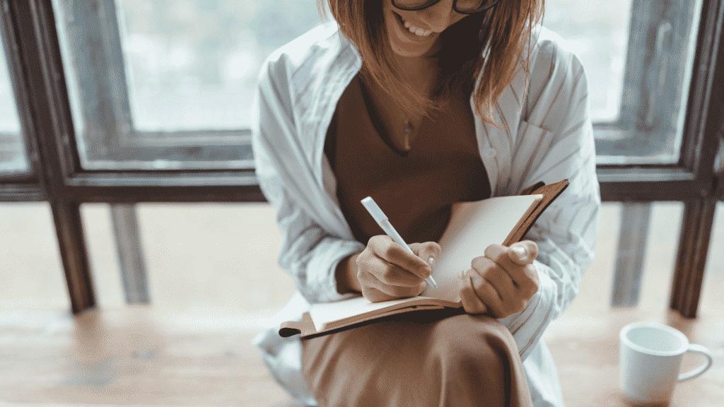 Mulher sorrindo enquanto escreve algo no seu caderno