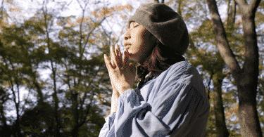 Mulher de chapéu com os olhos fechados fazendo um pedido no meio da floresta