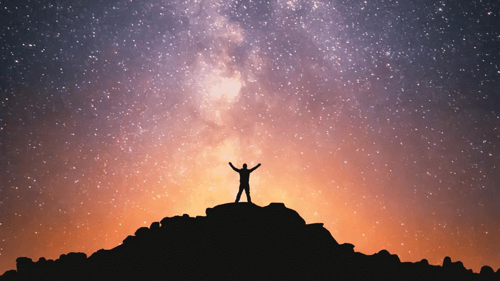 Silhueta de um homem no topo de uma montanha com os braços erguidos contemplando o universo