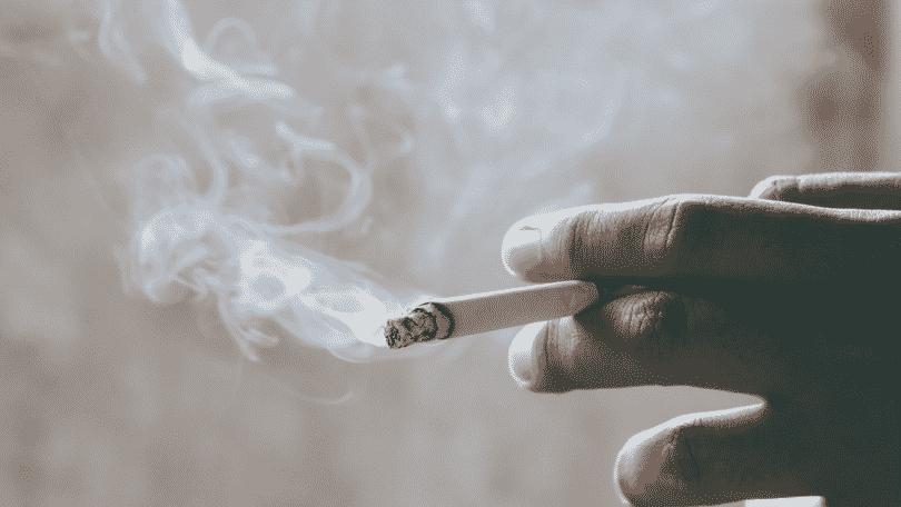Pessoa segurando cigarro entre os dedos