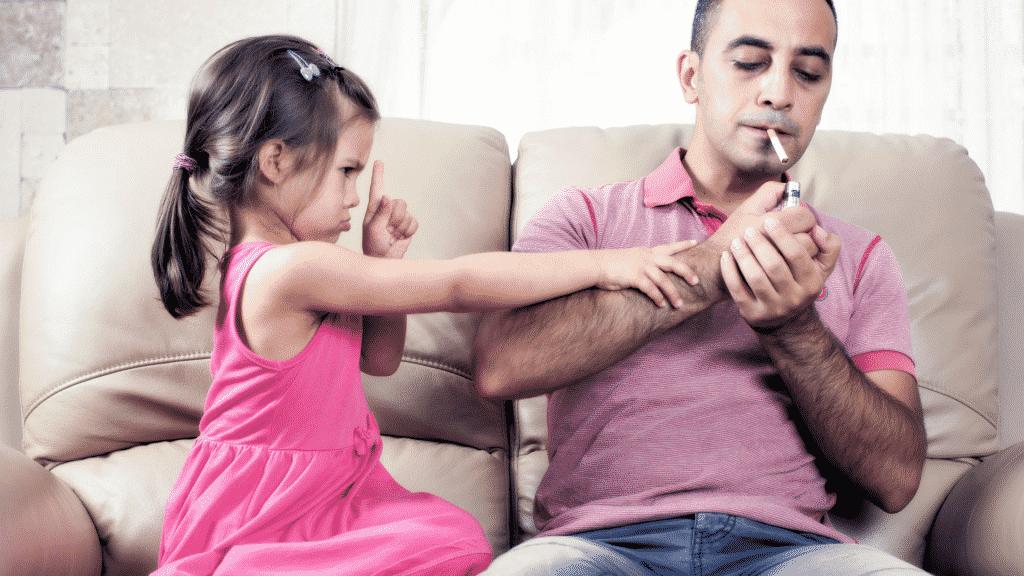 Homem acendendo cigarro e criança ao lado tentando impedir