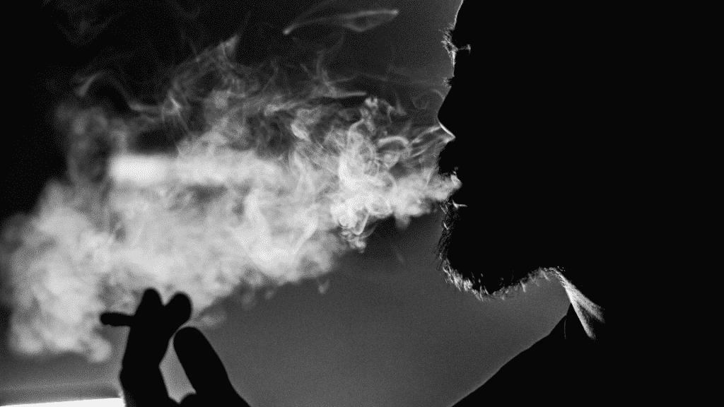 Foto em preto e branco de homem fumando