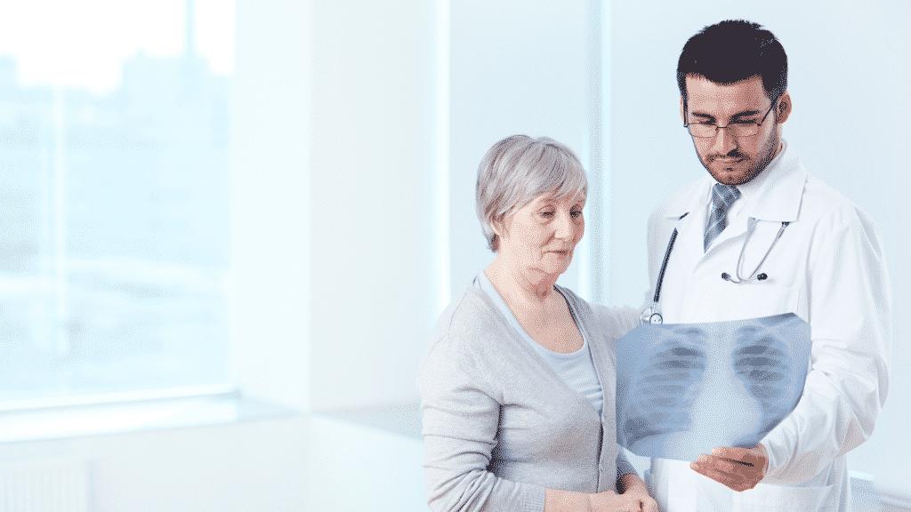 Médico e paciente olhando raio-x de pulmão