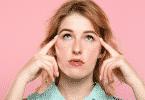 Mulher pensativa olhando para cima com os indicadores pressionando as têmporas