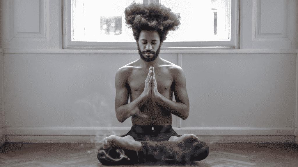 Homem meditando em casa.