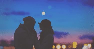 Silhueta de casal de mãos dadas com a vista noturna de uma cidade atrás
