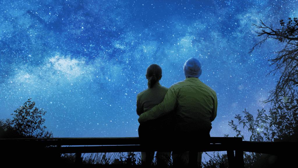 Silhueta de casal abraçados observando o céu noturno estrelado
