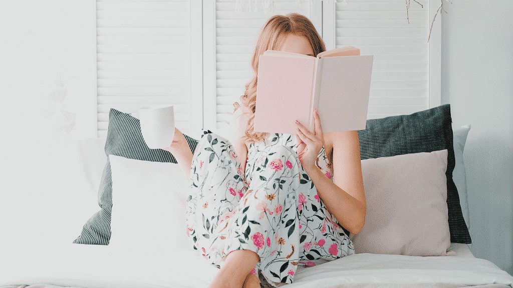 Menina lendo livro com xícara na mão