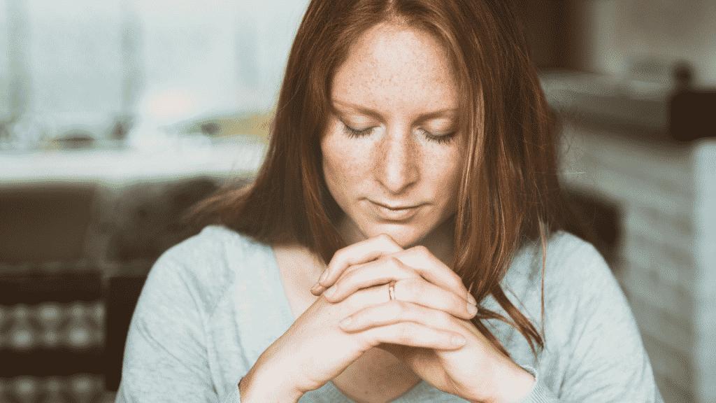 Mulher de olhos fechados orando em casa