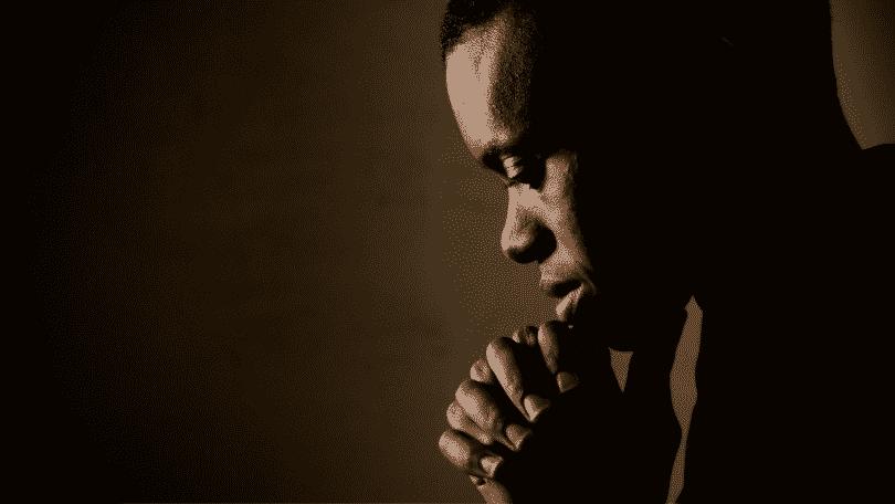 Homem de cabeça baixa orando