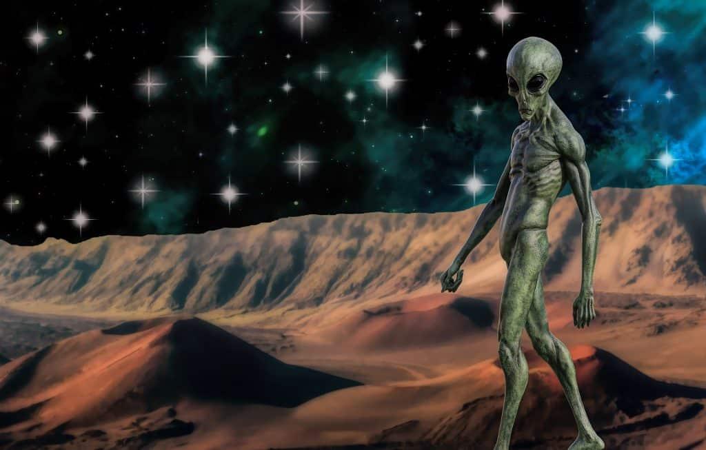 Imagem de um extraterrestre caminhando sobre o planeta. O céu está bem estrelado.