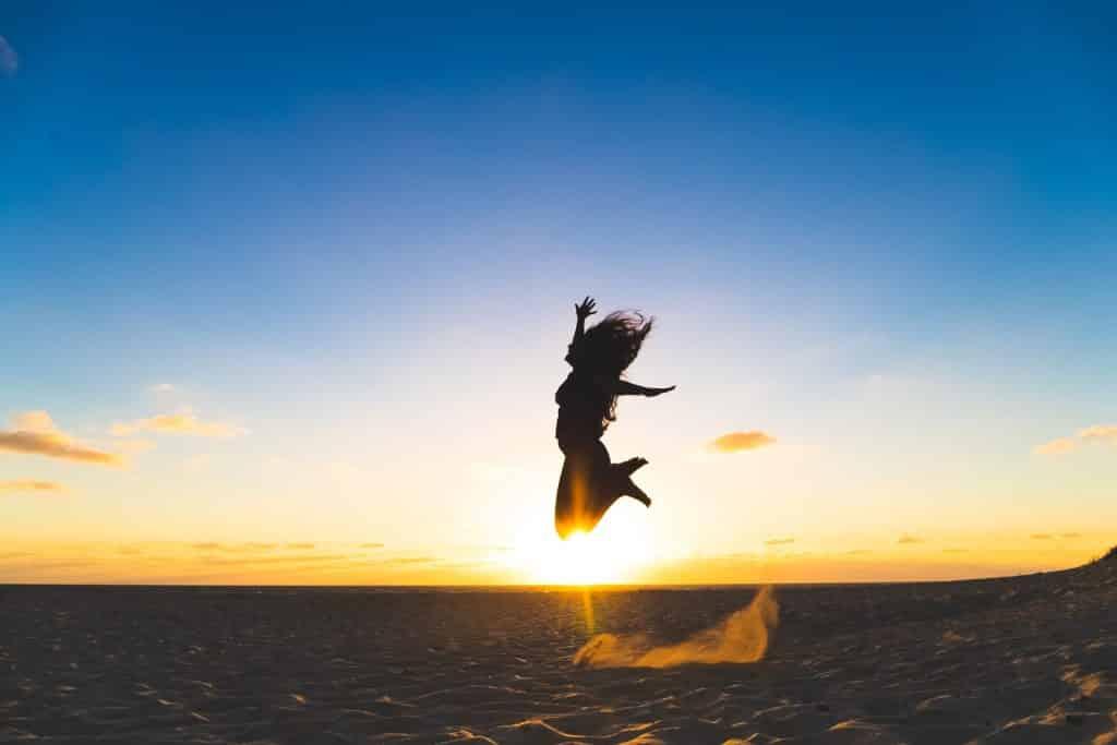 Silhueta de mulher pulando numa praia.