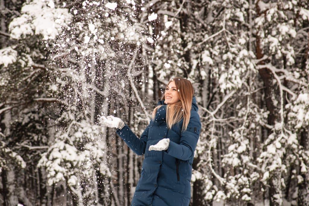 Imagem de uma floresta com suas árvores cobertas com neve. Em destaque temos uma mulher de cabelos claros e longos usando luvas e um casaco térmico na cor azul.