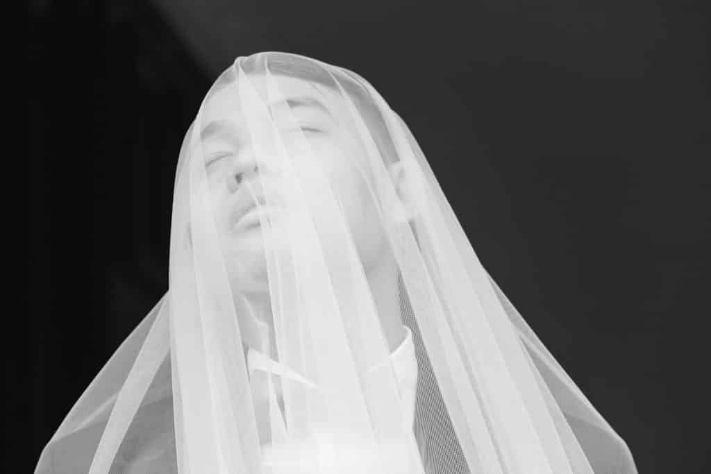 Homem de olhos fechados com a cabeça coberta por um véu branco.