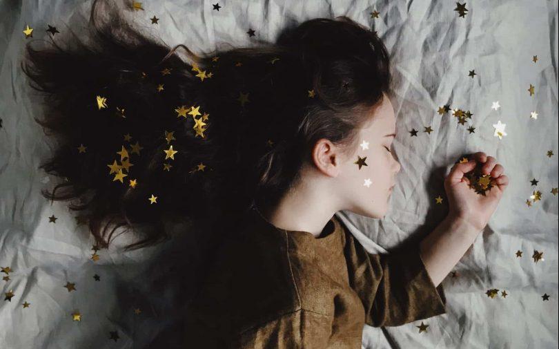 Imagem de uma linda garotinha usando um vestido marrom. Ela está dormindo em uma cama forrada com um lençol branco e sobre ela várias estrelas douradas.