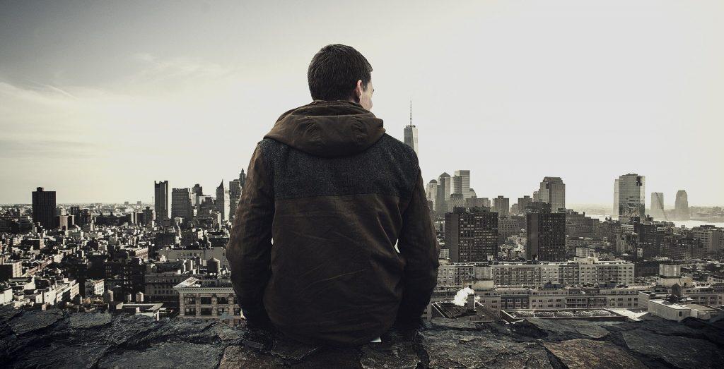 Imagem de um jovem sentado em uma mureta, olhando do alto para a arquitetura de muitos prédios de uma cidade.