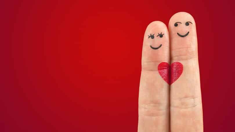 Imagem de fundo vermelho e em destaque dois dedos representando um casal. Um deles a mulher e o outro o homem. O que une os dedos é um desenho de um coração pequeno pintado na cor vermelha.