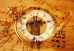 Imagem de fundo dourado de um relógio de bolso antigo. Em destaque um mapa astral desenhado sobre o relógio.