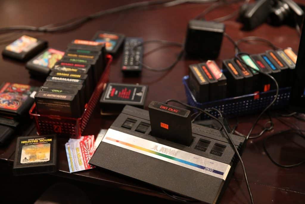 Imagem vintage do videogame Atari, disposto sobre uma mesa grande madeira e ao ado dele várias cestas contendo muitos jogos.