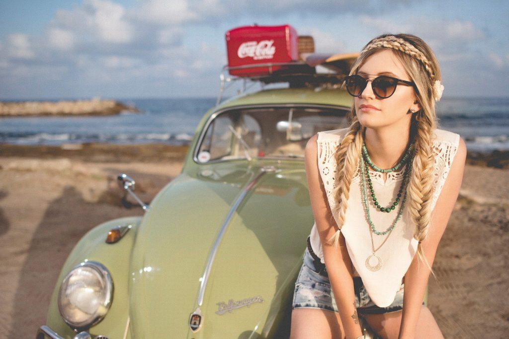Imagem com fundo de uma praia e o mar azul. Em destaque a imagem de um fusca vintage na cor verde claro. Sobre ele, um caixa vermelha com o logo da marca Coca Cola, escrito em branco e uma prancha de surfe. À frente do carro a figura de uma mulher estilo hippie, loura, com cabelos longos com duas tranças. Ela usa óculos escuros, colares, uma blusa branca, shorts jeans e uma flor na cabeça.
