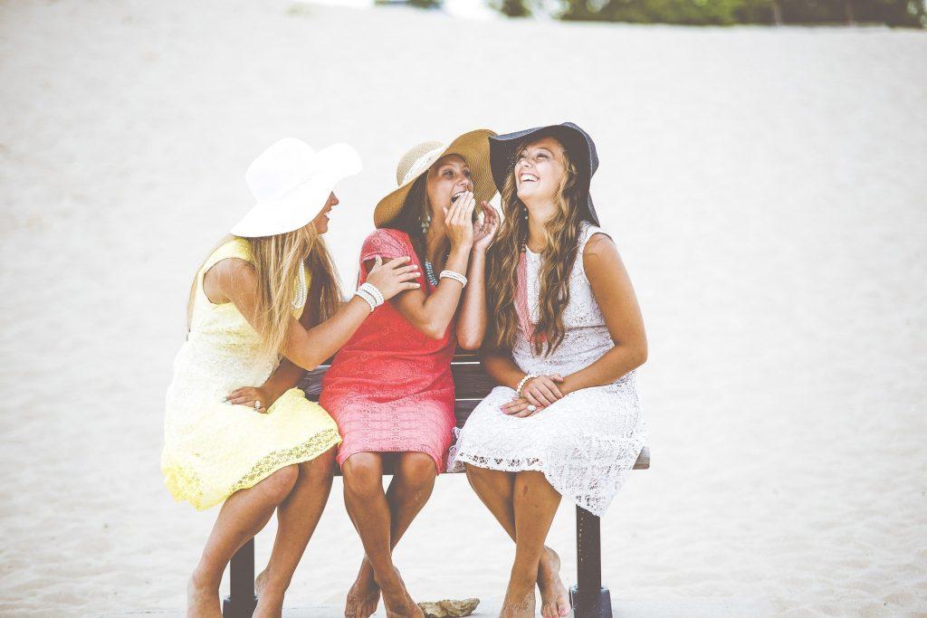 Imagem de três mulheres felizes e sorridentes. Elas estão sentadas em um banco de madeira. Todas vestem um vestido de renda   nas cores amarelo, vermelho e branco e chapéus de palha.