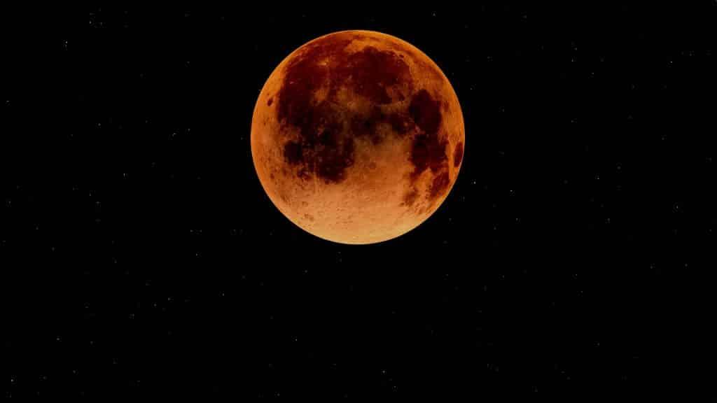 Imagem da super lua na cor alaranjada e ao fundo o céu estrelado.