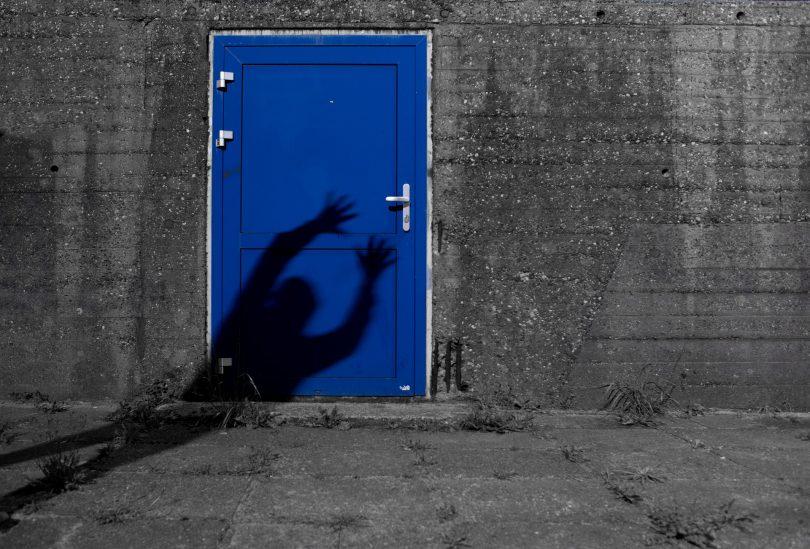 Imagem de uma parede cinza com a entrada para uma porta pintada na cor azul bic. Na porta consta a sombra de um fantasma que está querendo assombrar alguém.