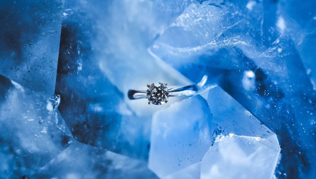 Imagem de fundo azul e em destaque um anel com uma linda pedra de água-marinha na cor azul.