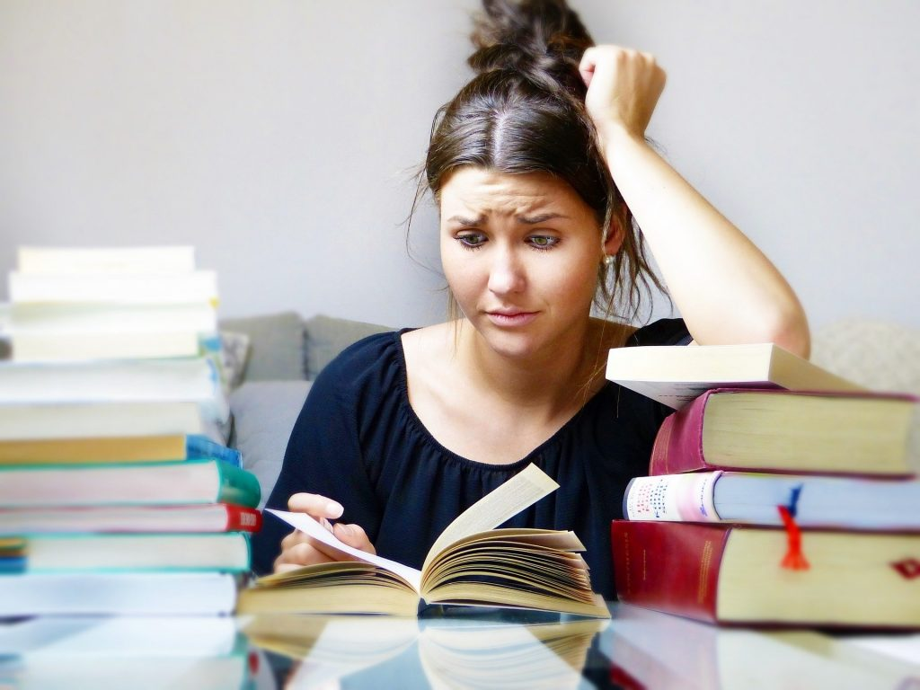 Imagem de uma mulher entre os livros. Ela está tentando se concentrar, mas não consegue porque sua mente está estressada.