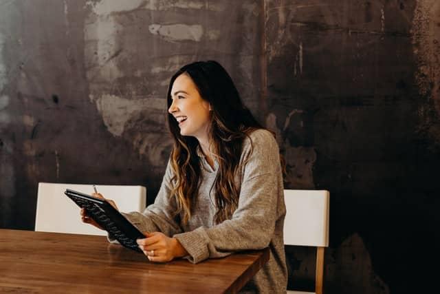 Mulher branca sentada segurando tablet preto.