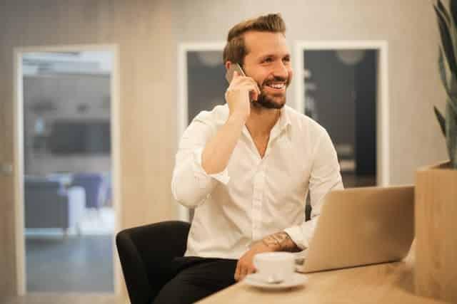 Homem branco sentado com celular no ouvido e notebook na mesa.