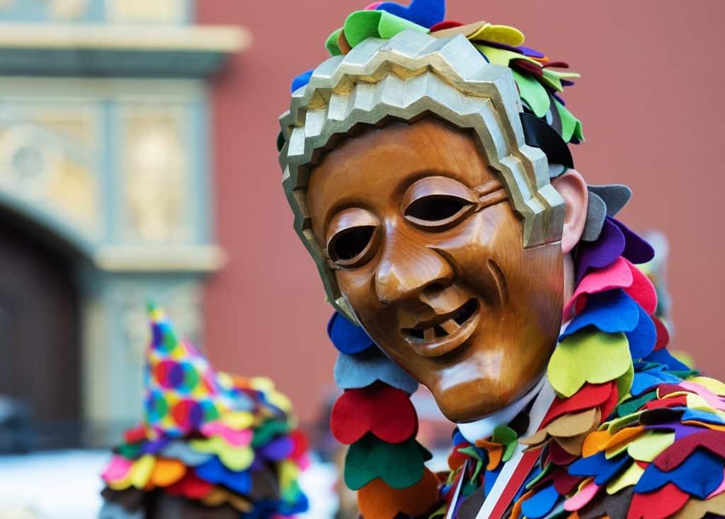 Imagem de uma pessoa fantasiada para o carnaval. A fantasia é colorida e ela usa uma máscara de madeira representando uma pessoa engraçada.