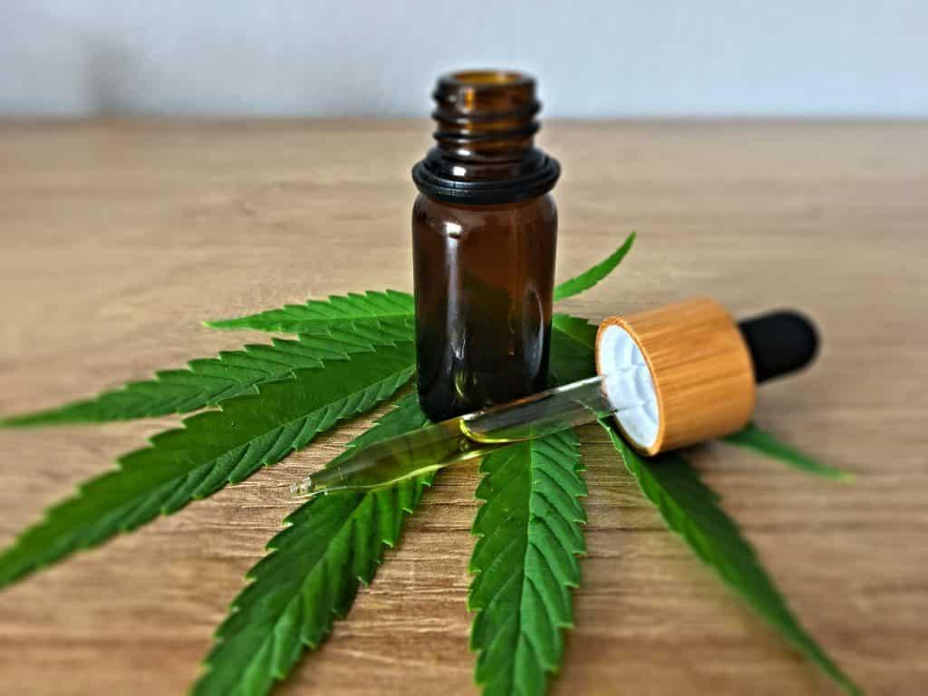Imagem de uma folha de maconha disposta sobre uma mesa de madeira e sobre a folha um pequeno vidro e um conta gostas com um pouco de óleo da erva dentro dele.