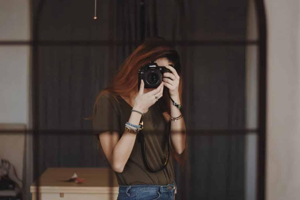 Mulher branca segurando câmera fotográfica em frente ao rosto.