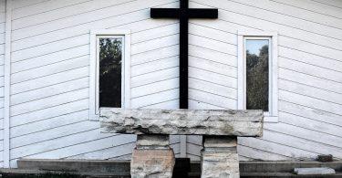 Imagem de fundo branco e em destaque uma cruz na cor preto e o lado dois quadros. À frente um mesa de pedra, representando o altar de uma igreja preparado para a quaresma.