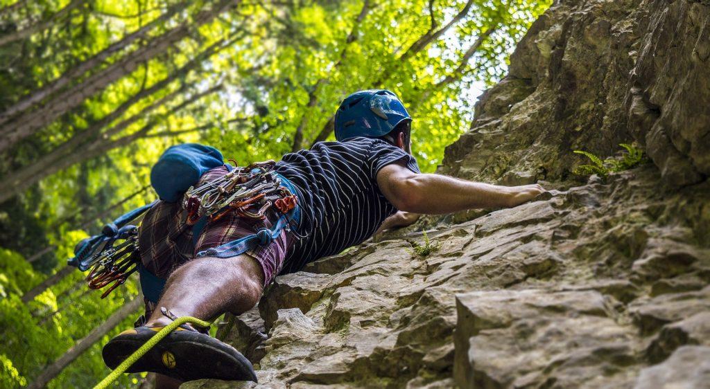Imagem de um homem escalando uma rocha. Ele usa equipamentos de segurança e um capacete na cor azul.