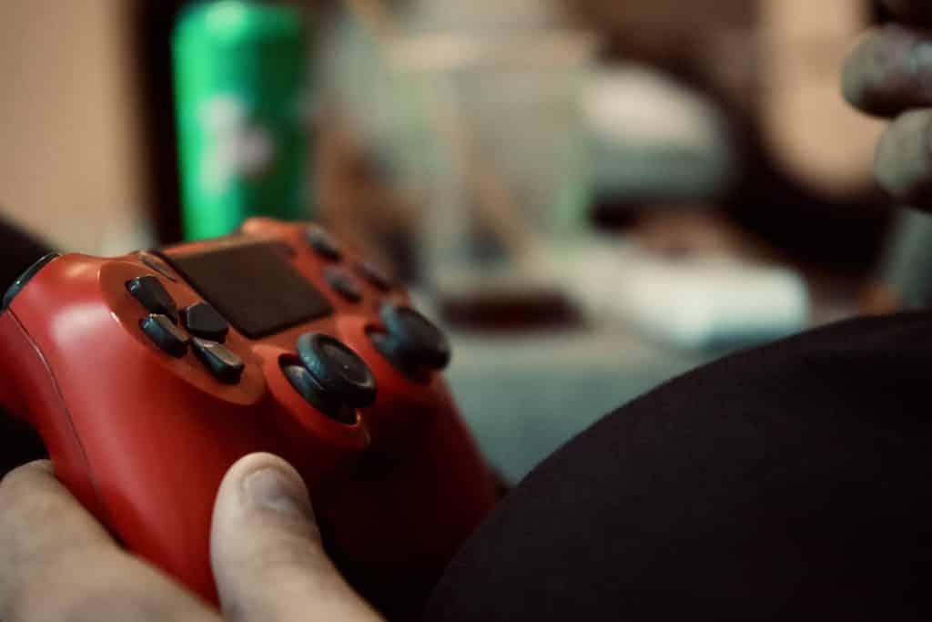 Imagem de um controle de videogame na cor vermelha sendo segurando por uma pessoa.
