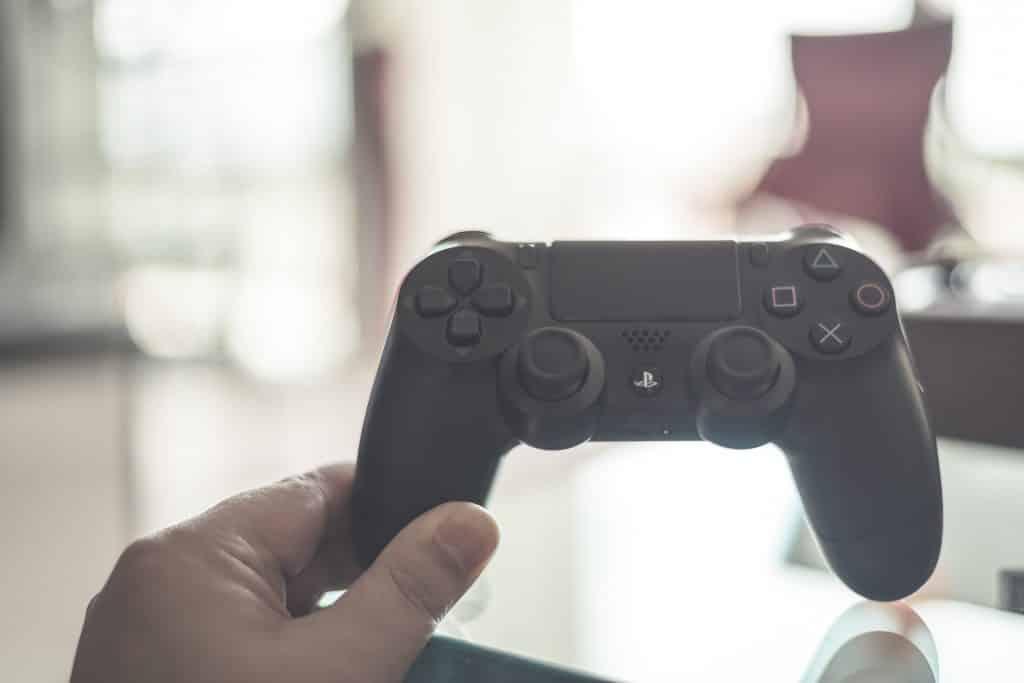 Imagem de um controle de videogame playstation sendo segurado por uma mão masculina.