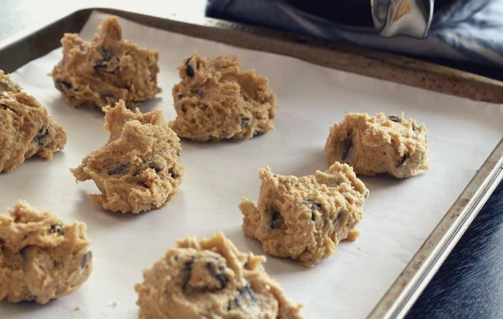Imagem de uma travessa de alumínio forrada com papel manteiga e sobre ela vários cookies indo para o forno.