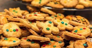 Imagem de duas travessas cheias de cookies todos decorados com açucar de confeiteiro.