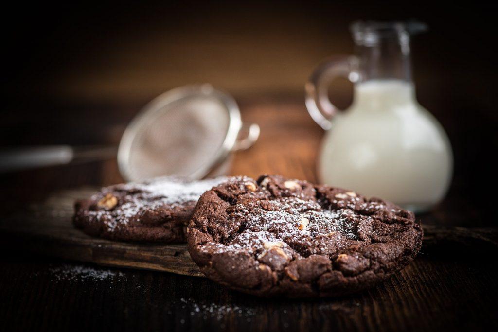 Imagem de cookies de chocolate cobertos com açúcar de confeiteiro, dispostos sobre uma mesa de madeira. Ao lado uma jarra com leite e uma peneira de alumínio.