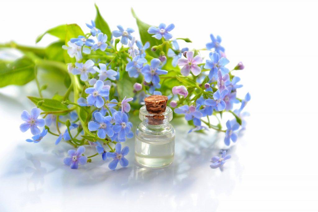 Imagem de um pequeno frasco de vidro contendo óleo essencial. Ao lado dele um ramo de flores pequenas na cor azul e roxo.
